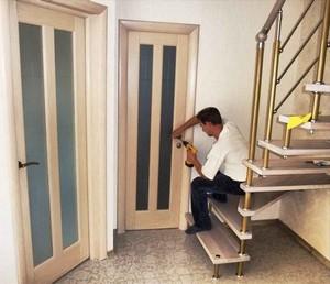 Мужчина заканчивает монтаж двери