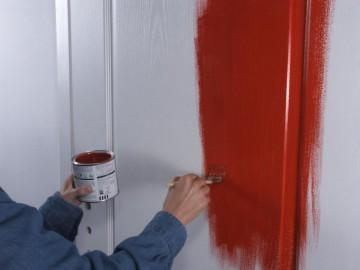 Красят деервянную дверь красным