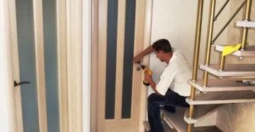 Мужчина прикручивает дверную ручку