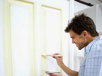 Парень красит дверь