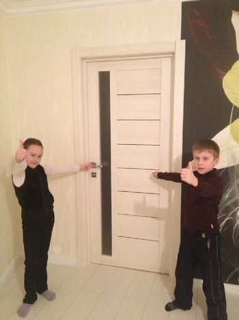 Дети рядом с дверью показывают ОК