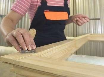 Девушка очищает поверхность деревянной двери
