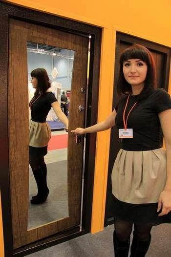 Девушка стоит у двери с зеркалом