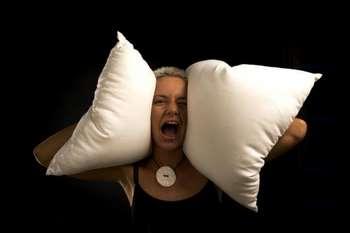 Девушка кричит и закрывает уши подушками