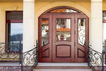 Большая входная дверь со стеклом и кованой решеткой