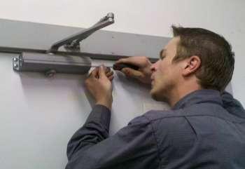 Мужик устанавливает дверной доводчик