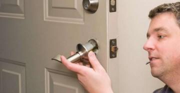 Мужик вставляет ручку замка в дверь
