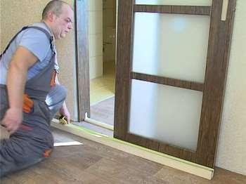 Мужик замеряет профиль для откатной двери