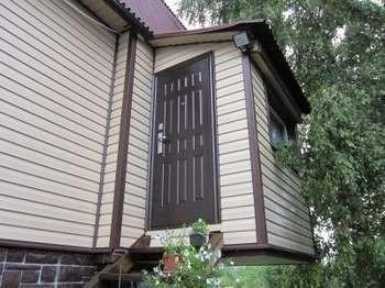 Входная дверь в дом под сайдингом