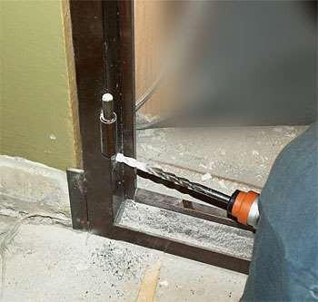 Мужик сверлит дверной косяк