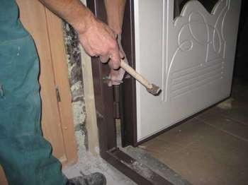 Мужик закрепляет дверную коробку