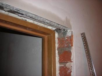 Угол дверного проема  в процессе отделки перфорированным уголком