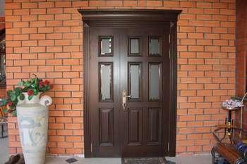 Входные деревянные двери в кирпичный дом