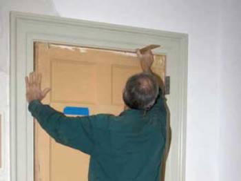 Мужик утепляет дверь